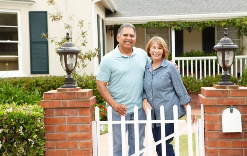two seniors in front of home preparing to downsize