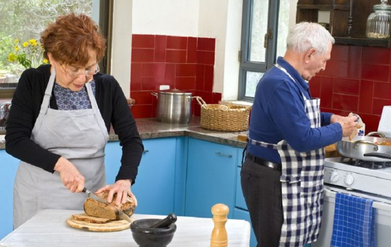 Senior couple preparing family tradions meal in kitchen