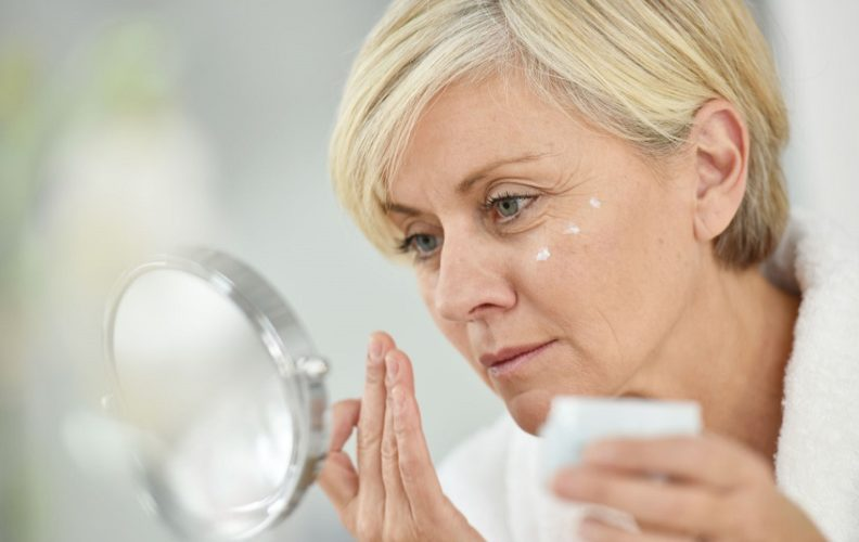 Senior woman caring for her aging skin
